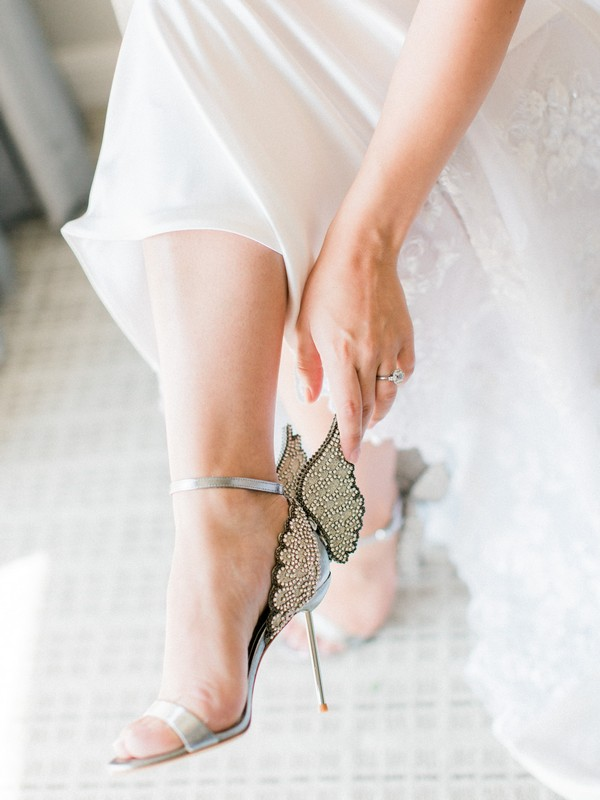 Bride putting on bridal shoes