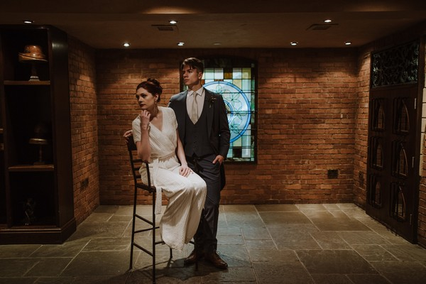 Groom standing next to bride sitting in chair in dark room