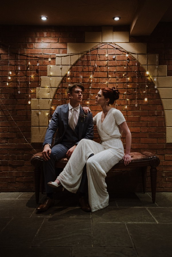 Bride and groom sitting in front of wall of fairy lights