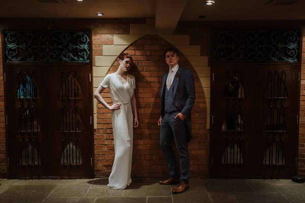 Bride and groom standing next to wall at Kilworth House