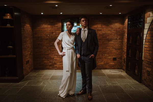 Bride leaning on groom's shoulder as he stands with hands in pockets