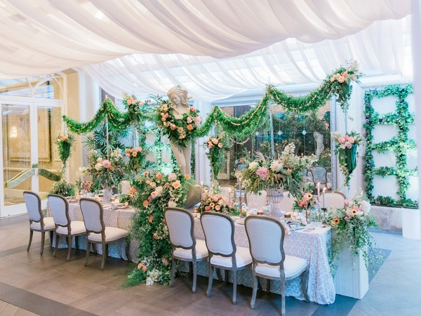 Wedding table display covered in flowers and foliage with statue centrepiece