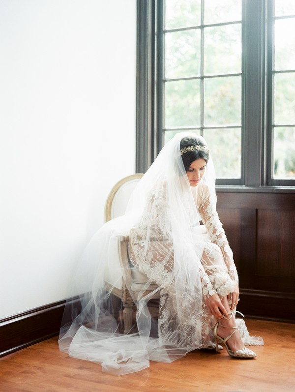 Bride sitting in chair putting on bridal shoes