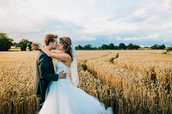 Bride and groom kissing in field of corn