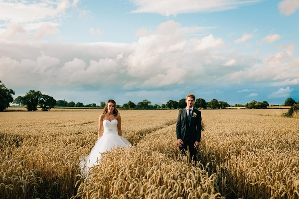 Bride and groom standing in cornfield