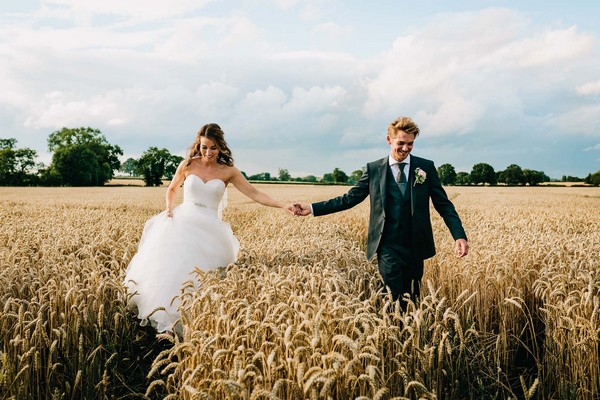 Bride and groom holding hands as they walk through cornfield