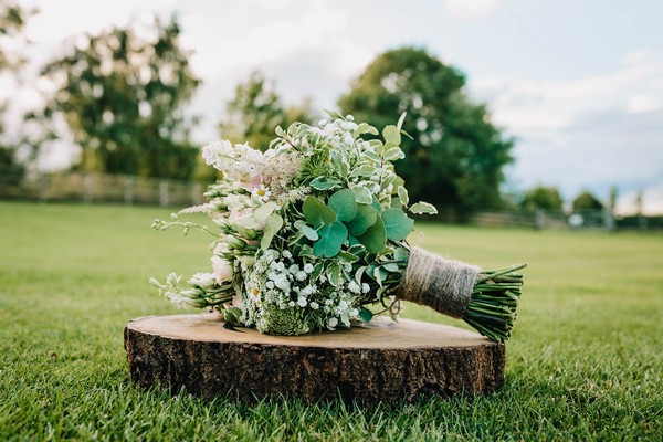 Bridal bouquet on log slice