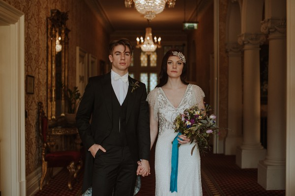 Bride and groom holding hands in hall of Kilworth House
