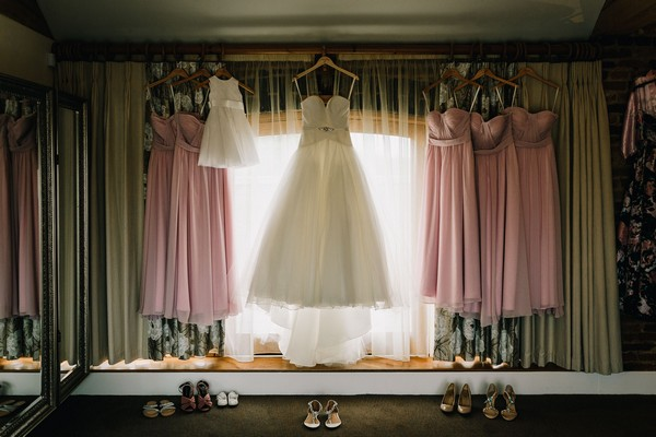 Wedding dress and pastel pink bridesmaid dresses hanging in front of window