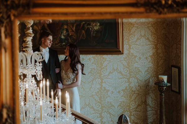 Reflection of bride and groom on stairs in mirror