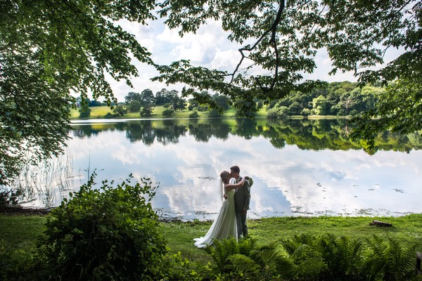 Bride and groom by lake at Combermere Abbey