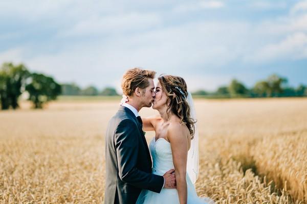 Bride and groom kissing in cornfield