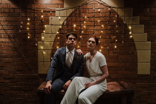 Bride and groom sitting in dark room in front of fairy lights