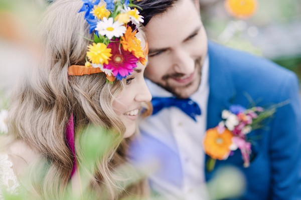 Bride with colourful floral headband resting head on groom