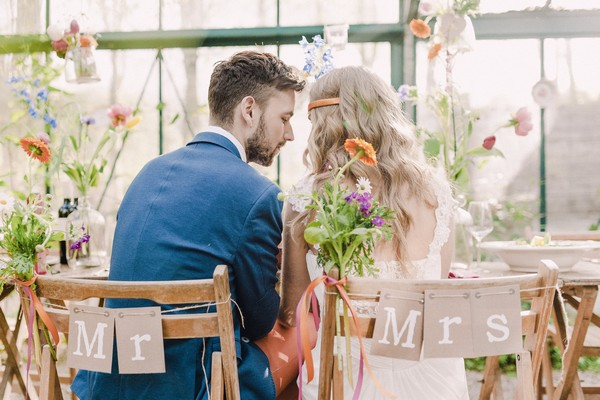 Bride and groom sitting on Mr and Mrs chairs