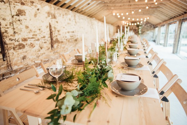 Long rustic wedding table with foliage table runner