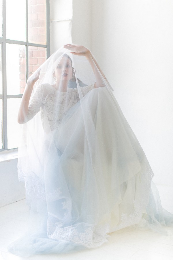 Bride sitting with veil over her head