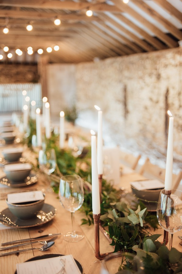 Candles and foliage lining centre of wedding table