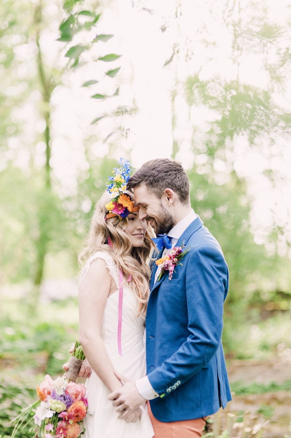 Groom in blue jacket with boho bride with colourful floral headband