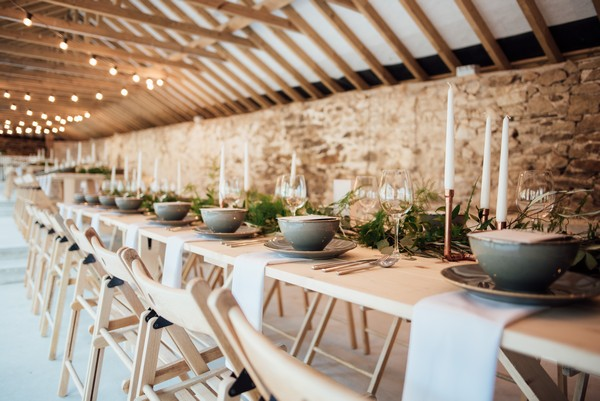 Long rustic wedding tables in The Cowyard Barn at Pengenna Manor
