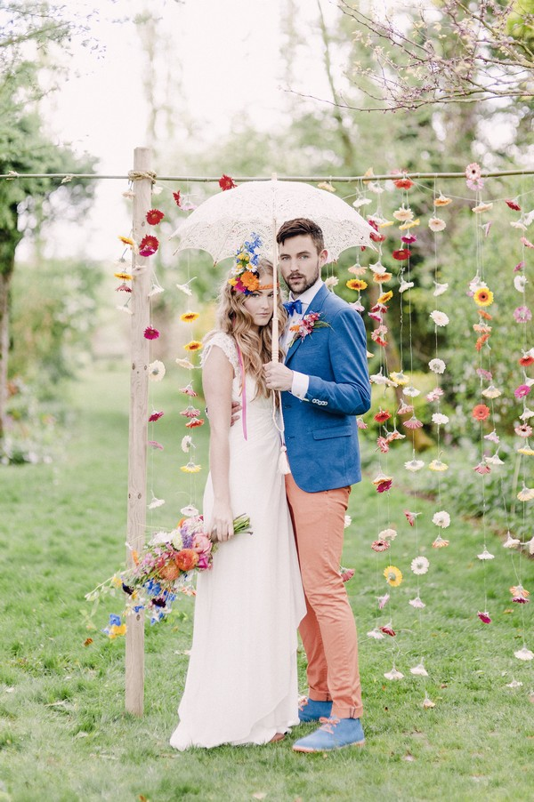Bride and groom with parasol standing in front of colourful suspended floral backdrop