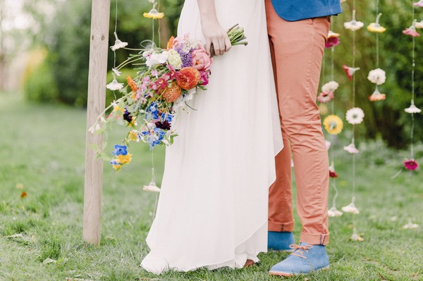 Bride holding colourful bouquet next to groom's coral trousers