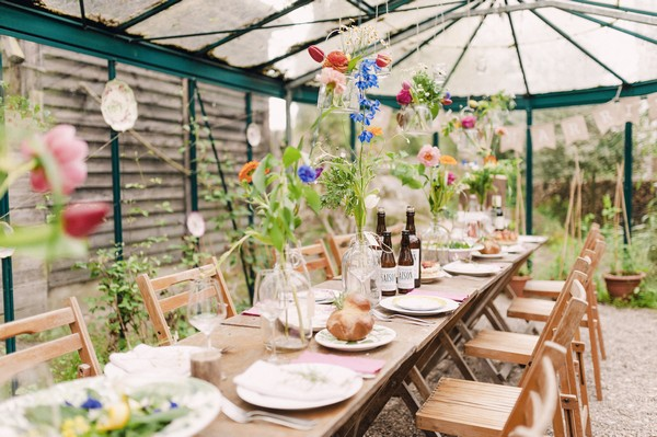 Rustic long long wedding table with colourful flowers