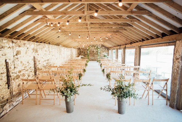 Rustic wedding ceremony set up at The Cowyard Barn at Pengenna Manor