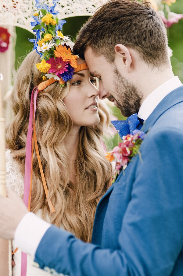 Boho bride with colourful floral headband touching heads with groom