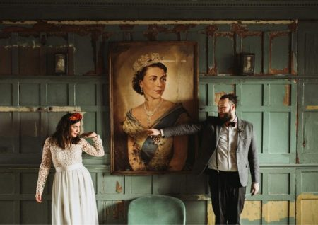Groom pointing at bride as they stand by picture of the Queen - Picture by Luke Hayden Photography