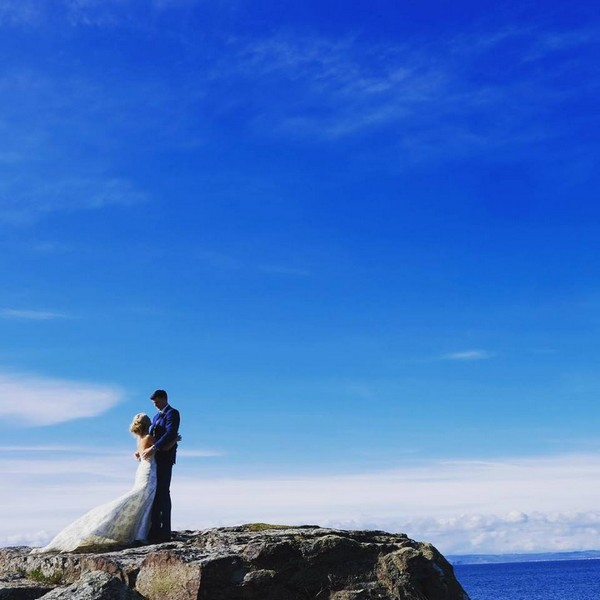Bride and groom on top of cliff by sea - Picture by Ashley-Liv Jamieson Photography