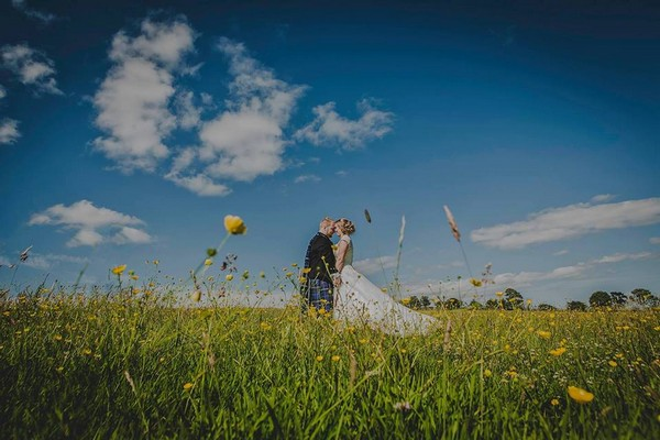 Bride and groom standing in a field of buttercups - Picture by Mike Cook Photography