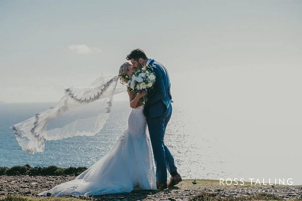 Bride and groom kissing by sea with bride's veil blowing in wind - Picture by Ross Talling Photography