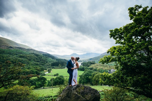 Bride and groom standing on rock with beautiful countryside behind them - Picture by Simon Biffen Photography