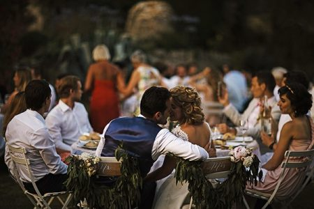 Bride and groom about to kiss at wedding breakfast table - Picture by Chris Barber Photography