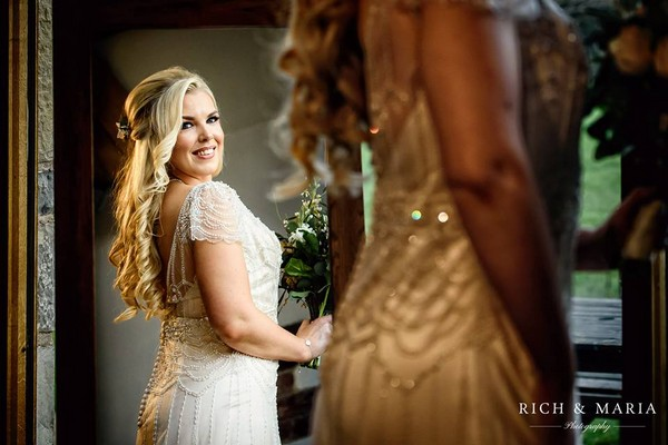 Bride looking at herself in the mirror - Picture by Rich and Maria Photography