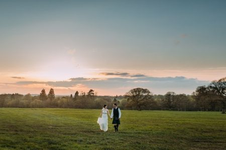 Bride and groom walking holding hands across a field - Picture by Eilidh Robertson Photography