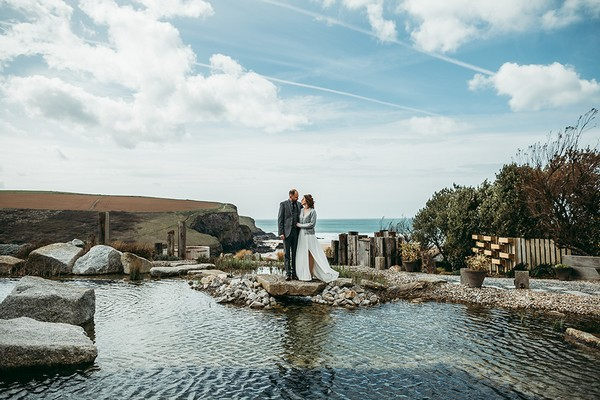 Bride and groom standing on rocks by pool of water - Picture by Tracey Warbey Photography