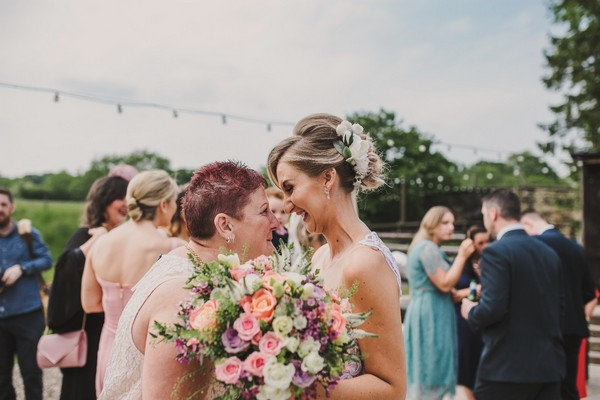 Bride with big smile as she stares into woman's eyes - Picture by The Struths