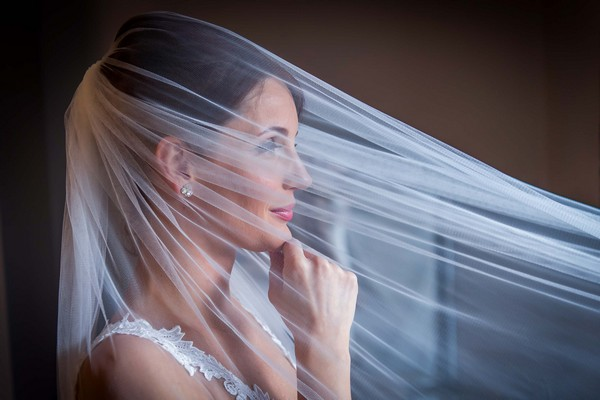 Bride with veil over her face and hand on her chin - Picture by Peter Anslow Photography
