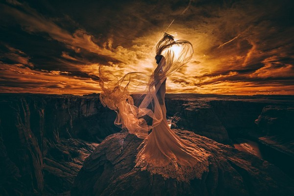 Dramatic picture of bride standing on rocks with sun shining through cloudy sky - Picture by Emin Kuliyev