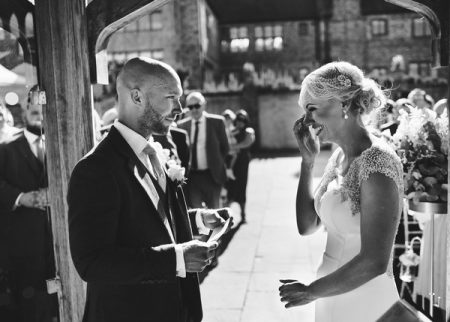 Bride wiping away tear after hearing groom's vosws during wedding ceremony - Picture by Rob Dodsworth Photography