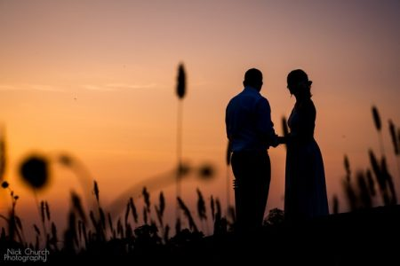 Bride and groom standing on hill at sunset - Picture by Nick Church Photography