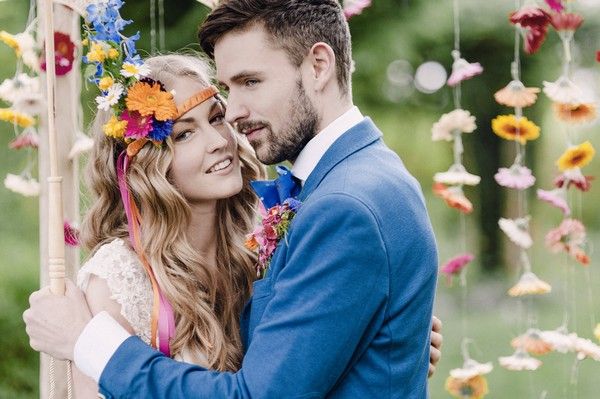 Bride with colourful floral headband and groom with blue jacket