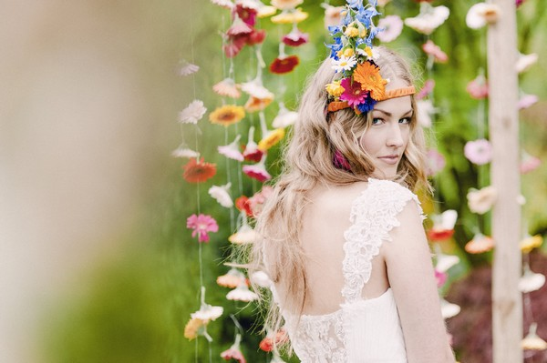 Boo bride looking over her shoulder in front of colourful suspended floral backdrop