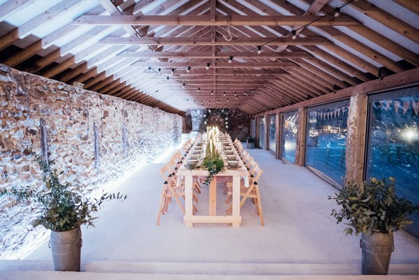 Long wedding tables in The Cowyard Barn at Pengenna Manor