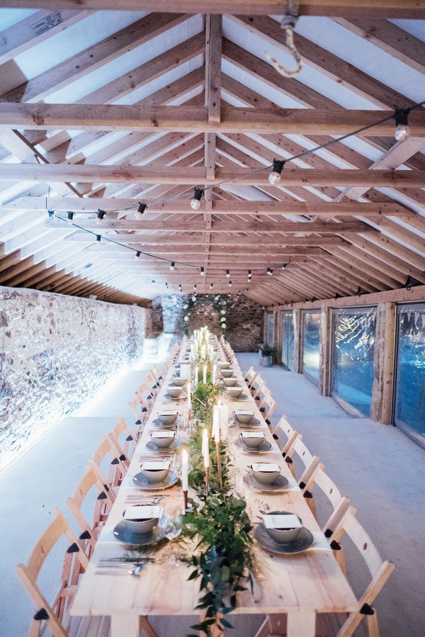 Long wedding tables in The Cowyard Barn at Pengenna Manor
