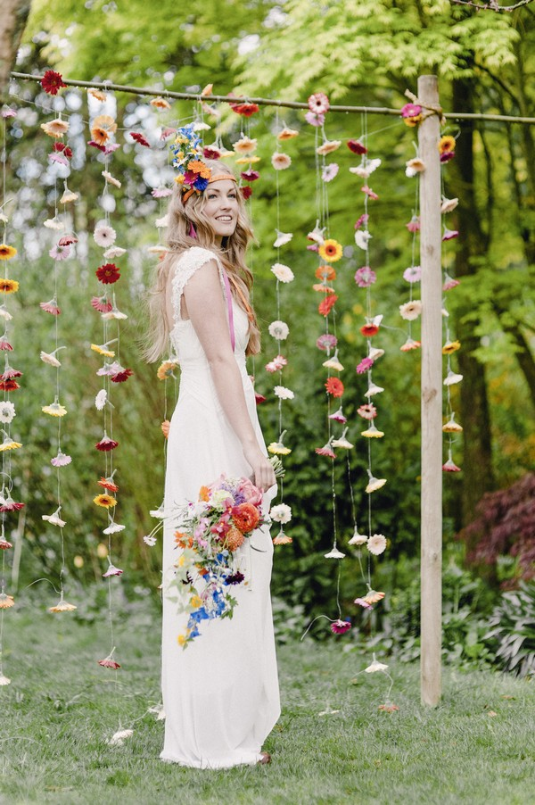 Boho bride in front of colourful suspended floral backdrop