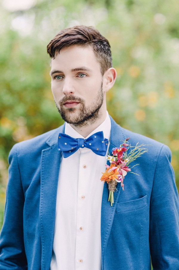 Groom wearing blue jacket and bow tie with colourful buttonhole