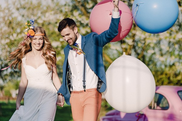 Bride with groom holding colourful balloons